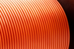 Orange copper wire cable in reels at factory, close up