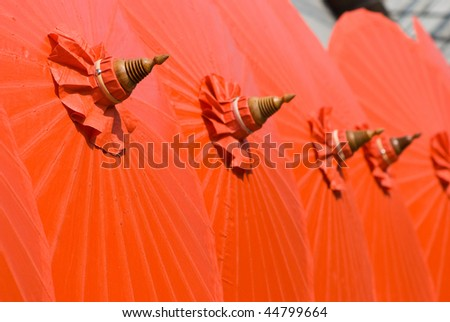 Orange cotton umbrellas at a handicraft festival in Bo Sang, Chiang Mai, Thailand. Shallow depth of field with the nearest umbrella in focus. - stock photo