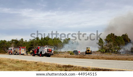ORANGE COUNTY, FL - JANUARY 8: Orange County and Florida Forestry Service fire fighters and their equipment stand by a controlled brush / forest fire on January 8, 2010 in Orange County, FL.