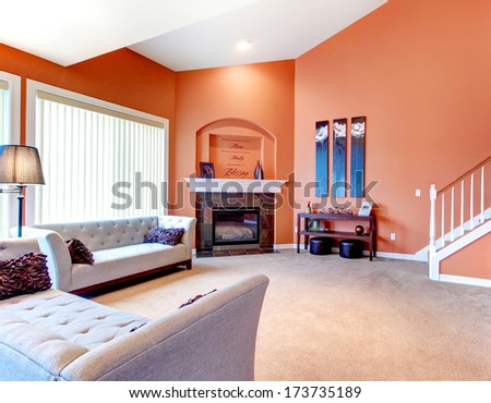Orange cozy living room with carpet floor, white wood stairs, grey furniture and fireplace. Decorated table with candles and wood wall handmade art
