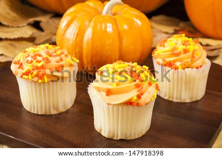 Orange cupcakes with pumpkins and colorful leaves