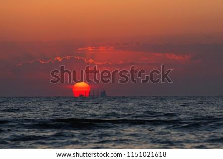 orange dawn, a big red sun and a ship on the horizon, a sea or an ocean