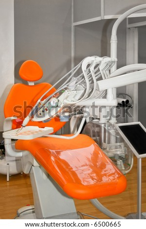 Orange dentist chair with bunch of equipment