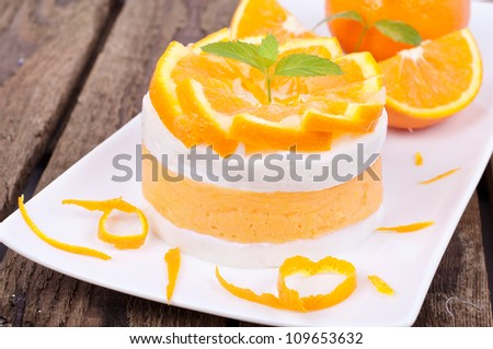 orange dessert with fresh fruits on a white plate on wooden board