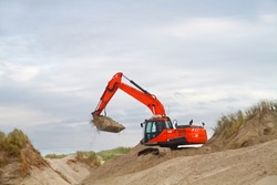 Orange digger working on recovery of dunes after wave attack, the beach of the Dutch island Terschelling