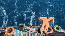 Orange diving wet suit hangs dry in sun of sailing motor yacht on blue sea. Scuba diving suits dry after dive. In background lifebuoy, buoys for mooring boat. Summer active underwater recreation