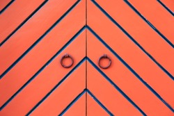 Orange double door and ring knockers. Diagonal black and blue stripes in fishbone pattern. Detail. In Tallinn, Estonia.