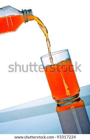 Orange drink pouring in glass with reflection on white background