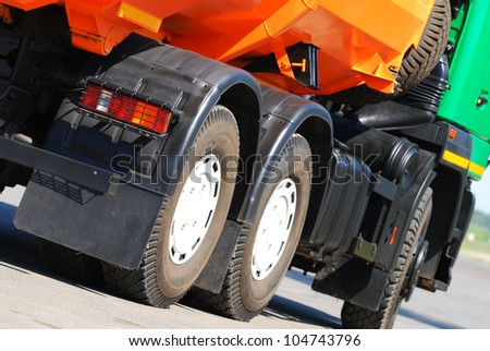 Orange dump truck chassis close to the road #104743796