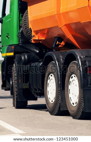 Orange dump truck chassis close to the road