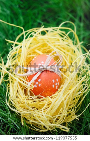 Orange Easter egg decorated with bow in a nest