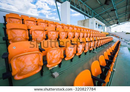 Orange empty seat of indoor stadium.