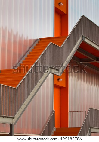 Orange escape stairs on the outside of a modern building