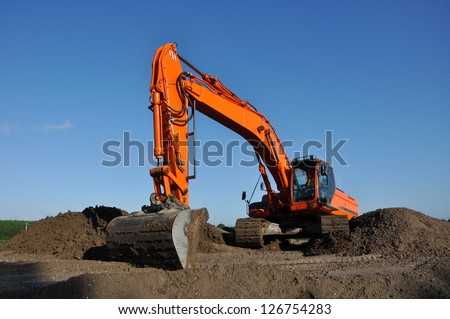 Orange excavator at work in open sand mine and a blue sky