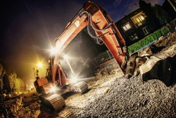 Orange excavator digger working at night on the street