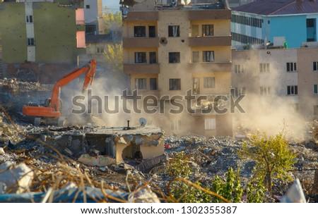 orange excavator in progress. heavy machine demolishing a building on a urban landscape. urban transformation