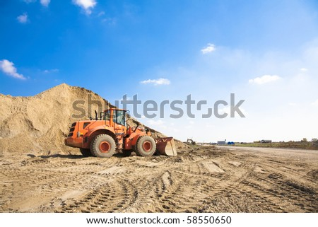 Orange excavator on a construction site working on a pile of gravel General construction scene