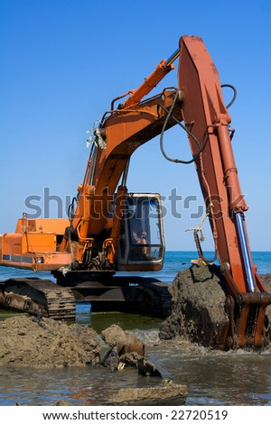 Orange Excavator on the beach - stock photo