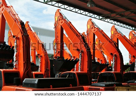 Orange Excavator or Backhoe parked under a roof  with a background of building and sky. Heavy Construction. #1444707137