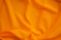 Orange fabric texture cloth blur display background. soft silk luxury smooth wave wallpaper. flat lay or top view with copy space. background for travel summer holidays concept.
