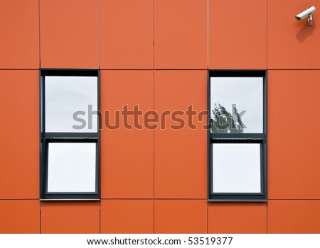 Orange facade of aluminum panels. Two windows and surveillance cameras, which looks onto the street. Close-up. Fragment.