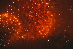 Orange festive fireworks on a black background. Abstract holiday background. International Fireworks Festival in Moscow