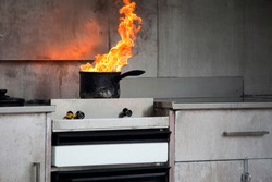 Orange flames rise from pot on a kitchen stove