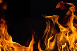 Orange flaming fire on black background. Flame looks dangerous and reverence. Background of fire that have space for some text.