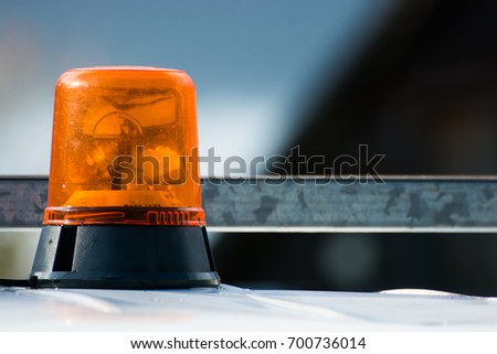 Orange flashing and revolving light on top of a support and services vehicle