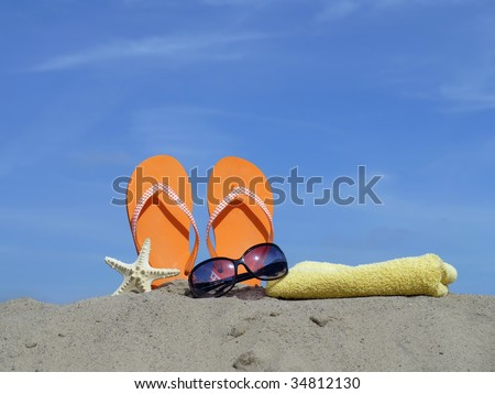 Orange flip-flops driven vertically into beach sand, starfish, sunglasses and yellow bath towel over blue sky