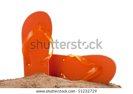 Orange flipflops in sand on a white background with copy space