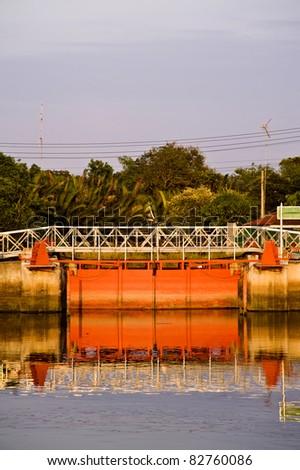 orange floodgate on the river - stock photo