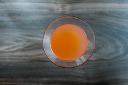 Orange fresh coctail juice in glass up view on wodden background.