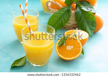 Orange freshly squeezed juice in glass and fresh fruits on a blue vivid background #1356332462