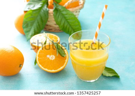 Orange freshly squeezed juice in glass and fresh fruits on a blue vivid background #1357425257