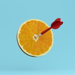 Orange fruit with circular target marked and red dart on pastel blue background. minimal idea food and fruit concept. An idea creative to produce work within an advertising marketing communications