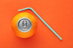 Orange fruit with pop up silver top of a can and a straw on orange background. Fresh orange juice and vitamins concept. Top view.