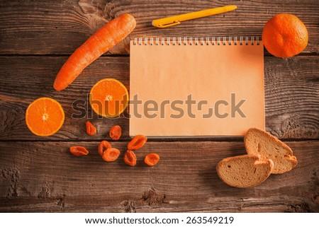 Orange fruits and vegetables on wooden background