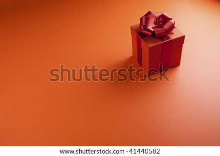 Orange gift box with a red tape