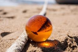 Orange glass ball on sand near the sea. Abstract conceptual photo.