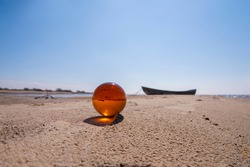 Orange glass ball on sand near the sea. Abstract conceptual photo.