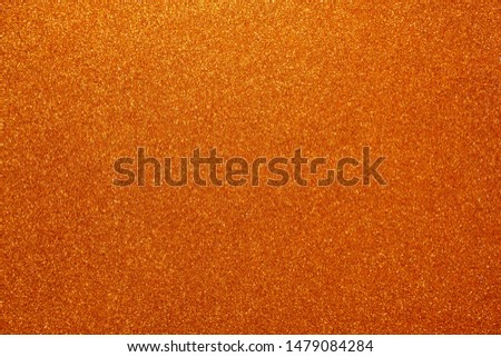 Orange glitter abstract shiny background. Design paper texture for decoration and design of Christmas, New Year or other holiday pictures. Beautiful packaging material.