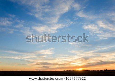 Orange glow of a sunset with a blue sky and white clouds over a green field with a forest in the background