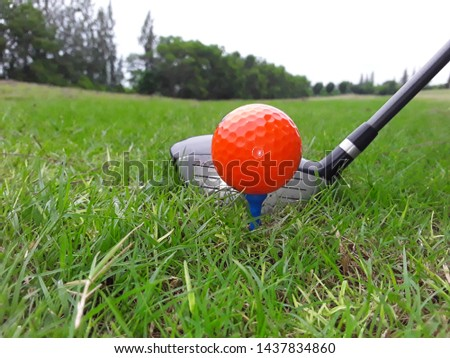 Orange golf ball on tee all ready drive
