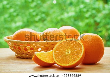Orange, half of orange, orange lobule and basket with oranges on the wooden table on the green blurred background