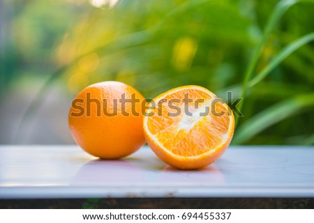 Orange, half of orange, orange lobule and basket with oranges on the wooden table on the green blurred background #694455337