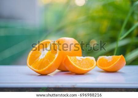 Orange, half of orange, orange lobule and basket with oranges on the wooden table on the green blurred background #696988216