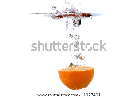 orange half splashing into water, against white
