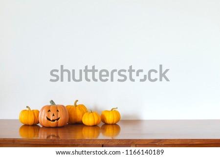 Orange halloween pumpkin on wooden table White wall background.