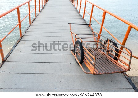 Orange handcart parked on pier walkway with iron railings, Handcart used for carriage of goods to ship. #666244378